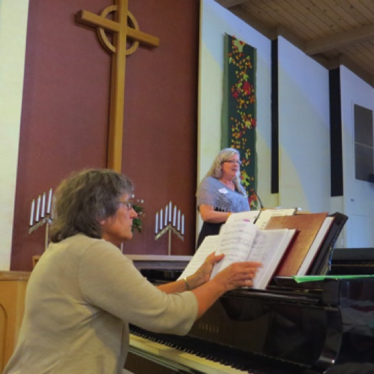 Our accompanist Pam, and Roberta reading a few notes from those who could not join us