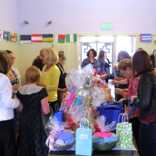 A crowd gathers around the raffle baskets
